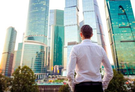Vista posterior del empresario mirando en el espacio de la copia mientras está de pie contra el rascacielos de cristal