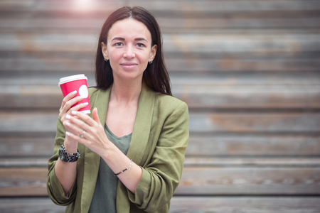 Woman drinking tasty coffee outdoors in the park Stock Photo