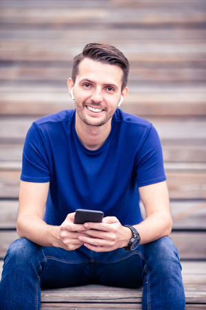 Man is reading text message on mobile phone while walking in the park Stock Photo