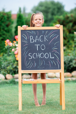 Happy little schoolgirl with a chalkboard outdoor Stock Photo