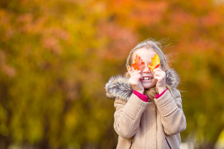 Adorable little girl at beautiful autumn day outdoors Stock Photo