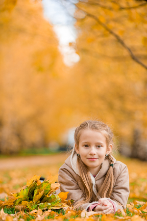 Portrait of adorable little girl outdoors at beautiful warm day with yellow leaf in fall Stock Photo