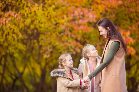 Little girl with mom outdoors in park at autumn day