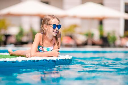 Beautiful little girl having fun near an outdoor pool