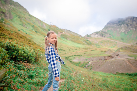 Beautiful happy little girl in mountains in the background of fog Stock Photo
