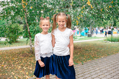 Two cute smilling little girls posing in front of their school. Stock Photo