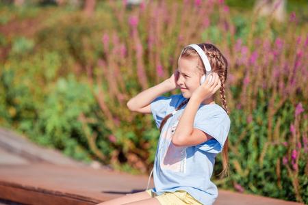 Little adorable girl listening music in the park Stock Photo