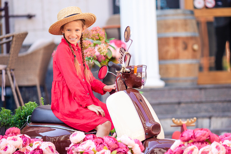 Adorable little girl in hat on the moped outdoors