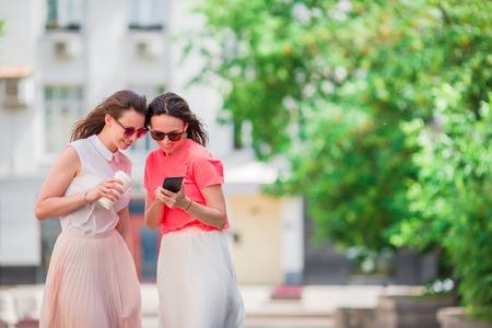 Happy young women walking along city street. Stock Photo