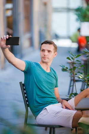 Caucasian tourist with smartphone taking selfie sitting in outdoor cafe. Stock Photo