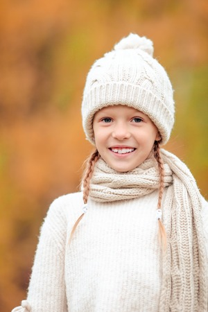 Portrait of adorable little kid with yellow leaves in fall. Autumn time