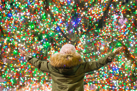 Happy girl on the background of the Rockefeller Christmas tree in New York Stock Photo