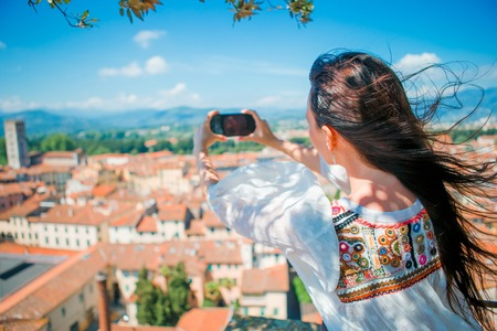 Young caucasian woman making photo of european old city by mobile phone from the observation place Stock Photo