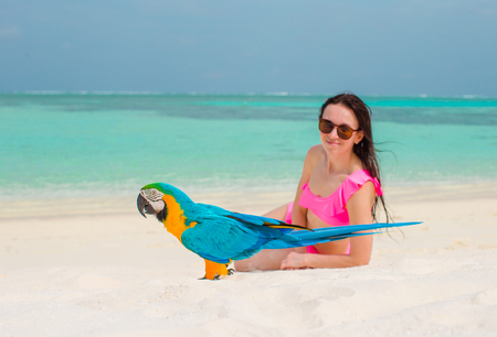 Adorable girl at beach with colorful parrot Stock Photo