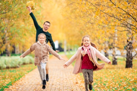 Family of dad and kids on beautiful autumn day in the park Stock Photo