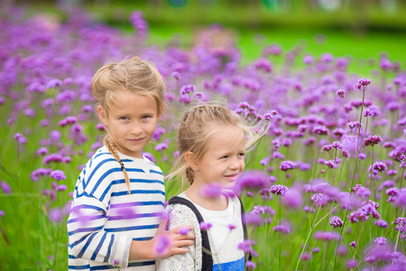 Little adorable girls walking outdoors with flowers