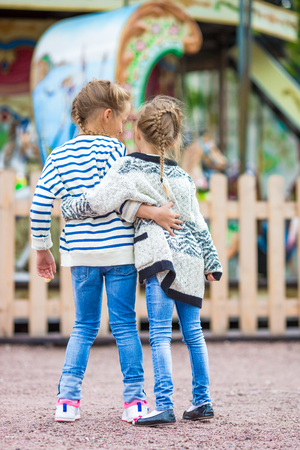 Adorable little girls near the carousel outdoors Stock Photo