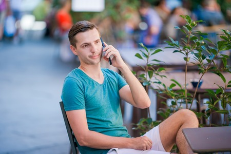 Caucasian boy is holding cellphone outdoors on the street. Man using mobile smartphone.