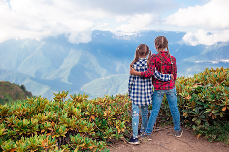 Beautiful happy little girls in mountains in the background of fog Stock Photo