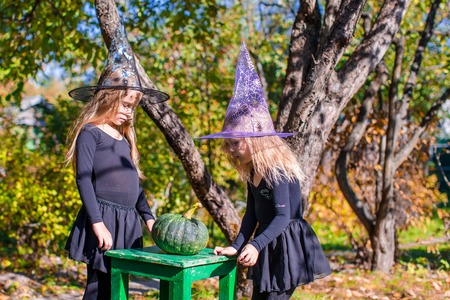 Adorable little witches have fun outdoors on Halloween. Trick or treat.