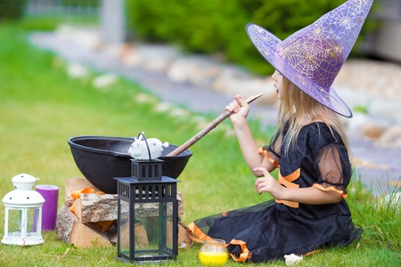 Happy little witch have fun outdoors on Halloween. Trick or treat. Stock Photo