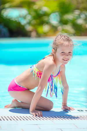 Little active adorable girl in outdoor swimming pool ready to swim Фото со стока
