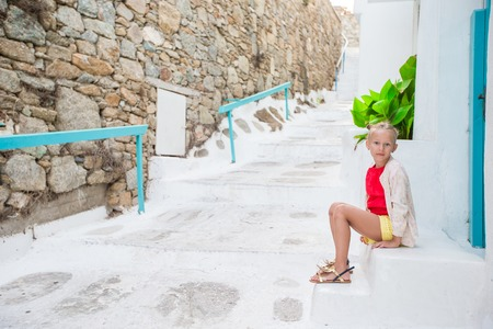 Little girl portrait outdoors in old greek village. Kid at street of greek village with white walls and colorful doors