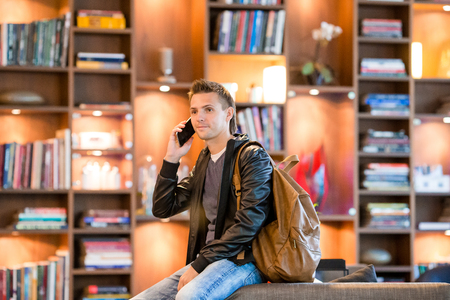 Young man taking by smartphone in bookstore Stock Photo