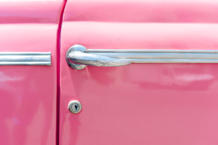 Closeup of classic pink vintage car in Old Havana, Cuba. The most popular transportation for tourists are used as taxis.