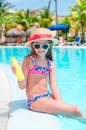 Little girl with bottle of sun cream sitting on the edge of swimming pool Banco de Imagens - 112900463