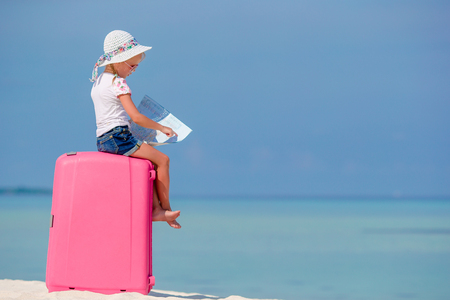 Little tourists girl with big suitcase on tropical white beach