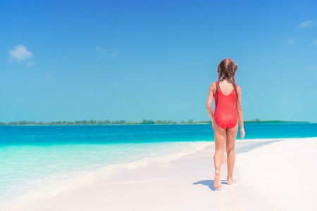 Adorable little girl walking along white sand Caribbean beach
