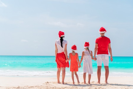 Happy family on the caribbean beach celebrating Christmas vacation