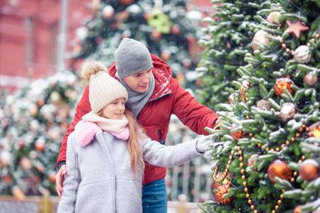 Little happy girl near fir-tree branch in snow for new year. 版權商用圖片
