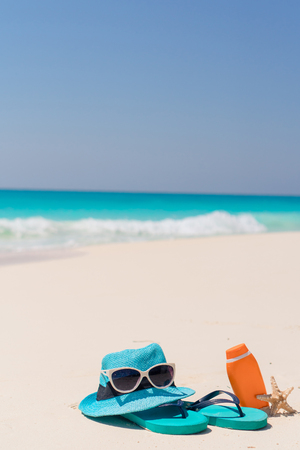 Suncream bottles, goggles, starfish and sunglasses on white sand beach background ocean Stock Photo