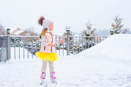 Adorable girl skating on ice rink outdoors in winter snow day