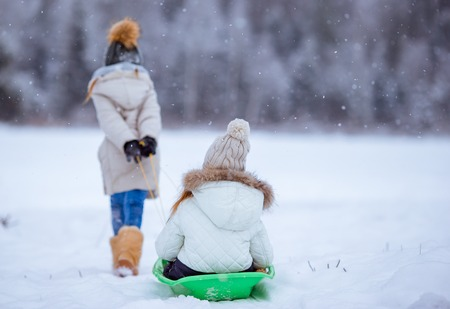 Adorable little happy girls sledding in winter snowy day.
