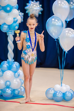 Little gymnast with her sports awards on the carpet in rhythmic gymnastics