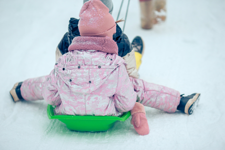Adorable little happy girls sledding in winter snowy day. Banque d'images - 115534253