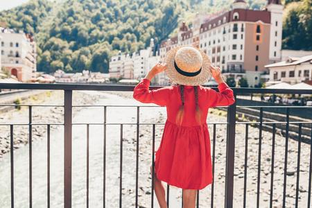 Kleines Mädchen am Hut am Ufer eines Gebirgsflusses in einer europäischen Stadt. Standard-Bild