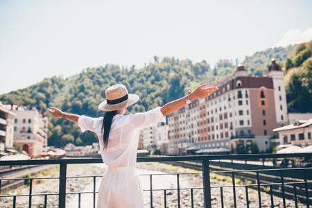 Glückliches Mädchen am Hut am Ufer eines Gebirgsflusses in einer europäischen Stadt.