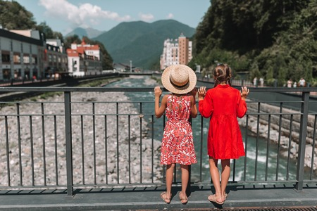 Back view of girls on the embankment of a mountain river in a European city. 写真素材 - 115534594