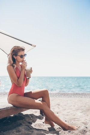 Young woman with cocktail glass on white beach sitting on sunbed