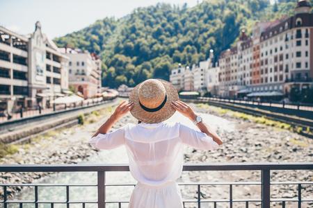 Schöne Frau mit Hut am Ufer eines Bergflusses in der Stadt. Standard-Bild