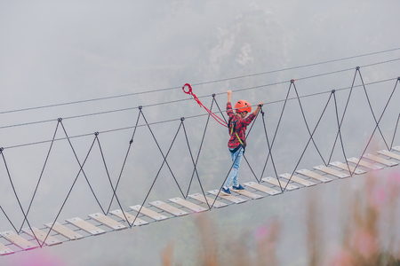 The rope bridge on the top of mountain of Rosa Khutor, Russia. Little brave kid on a pendant bridge over an abyss in the mountains Stock Photo