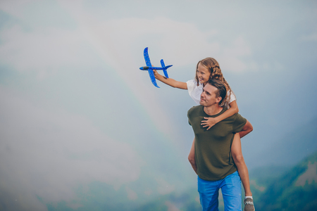 Beautiful little girl and young father in mountains in the background of fog
