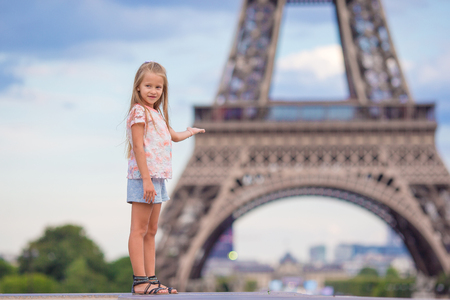 Adorable toddler girl in Paris background the Eiffel tower during summer vacation Stock Photo