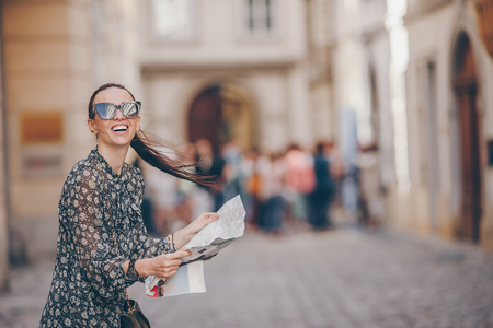 Young woman with a city map in city. Travel tourist girl with map in Vienna outdoors during holidays in Europe. Stock Photo