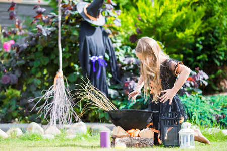 Happy little witch outdoors on Halloween. Trick or treat.