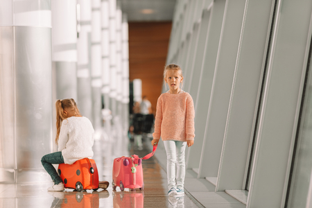 Adorable little girls having fun in airport sitting on suitcase waiting for boarding Stock Photo